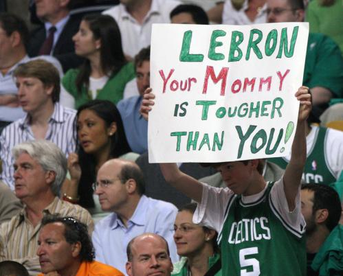 A Celtics fan holds another sign directed at LeBron James.