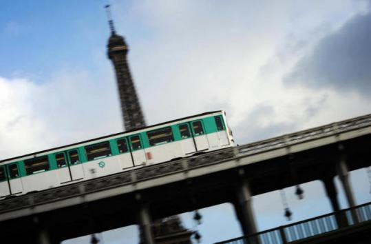 A train of the Paris Metro (cheaper than a taxi) passes the Eiffel Tower.