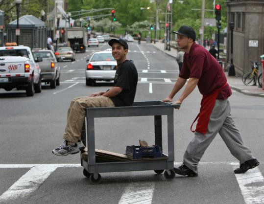 Joelson Silva (left) and Steven Wilson finished up a food delivery run to Beacon Hill yesterday, with Wilson giving his co-worker a ride on the cart across Tremont Street in Boston.