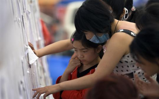 Earthquake victims looked at a missing person's list, trying to find a family member at a stadium that has become a refugee camp in China's Sichuan province. The government is struggling to shelter the 5 million people left homeless by the May 12 quake.