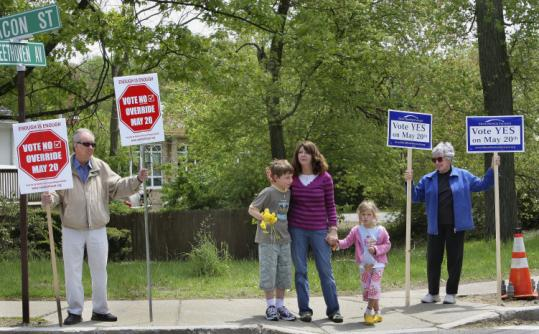 Newton residents made their opinions heard on Beacon Street. In center is Carla Brigham, with her son Lucas, 7, and daughter Maisie, 5. She was voting yes. On left is Larry Young, voting no, and on far right is Maggie Blacher, voting yes.