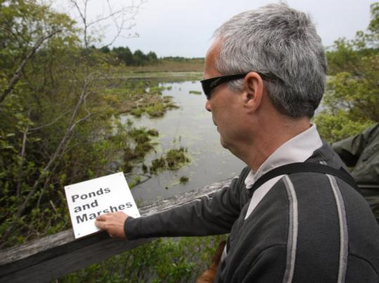 Jerry Berrier, who helped make an audio tour for the Sensory Trail in Norfolk, reads a Braille sign along the walk.