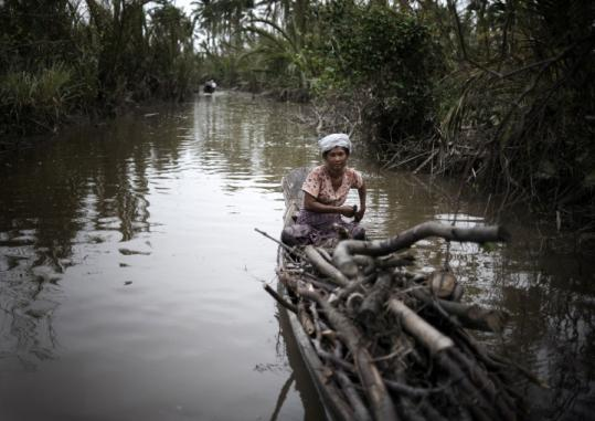 A woman salvaged wood to be used for cooking in the Irrawaddy Delta region of Burma on Friday.