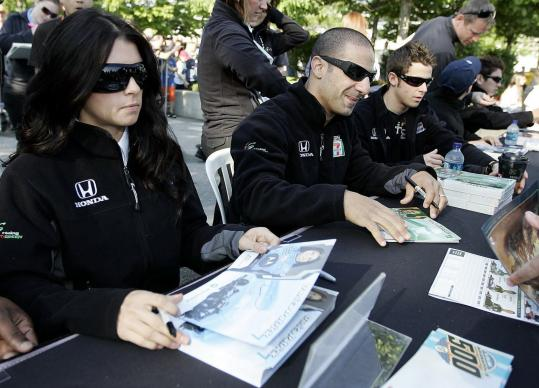 Danica Patrick, Tony Kanaan (center), and Marco Andretti sign autographs before yesterday's meeting of the drivers.