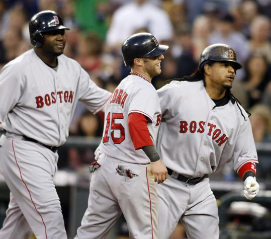 After homer No. 499, Manny Ramírez (right) is escorted to the dugout by passengers David Ortiz (left) and Dustin Pedroia.