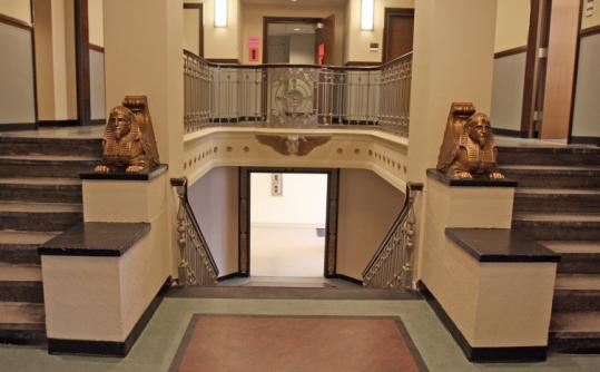 The clinic's lobby is rich with symbols of death. Two sphinxes guard stairs that once led to the morgue's storage drawers.