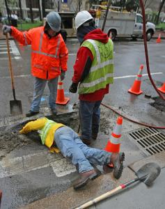 Marty Kilgullen (foreground) and Bill Mayer observed as Aaron Ferreira cleaned a gas pipe on Congress Street April 28.