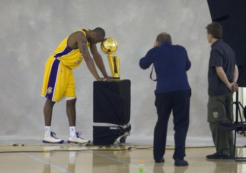 Kobe Bryant rests his head on the championship trophy while posing for a