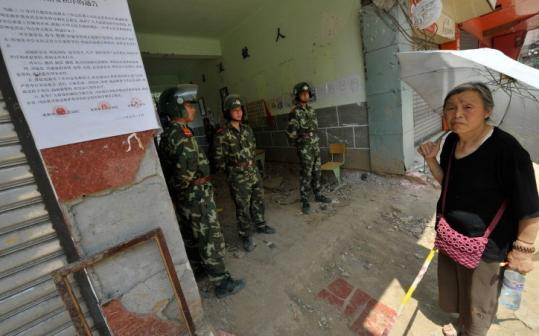 Police and soldiers in Dujiangyan, in China's southwestern province of Sichuan, yesterday blocked access to a school destroyed in last month's earthquake. Residents reported angry protests by grieving parents.
