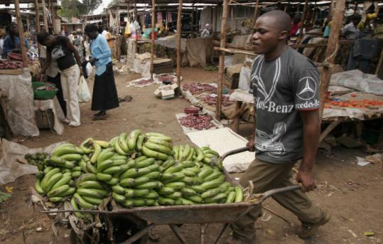 Among the keys to overcoming problems in food prices and scarcity would be increasing local production of crops in such African nations as Kenya, where a vendor transported bananas through a Nairobi market yesterday.