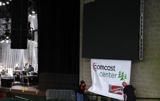 Workers on the main stage in Mansfield hung a Comcast Center banner yesterday under one of the video screens.