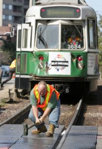 A worker scrambled to fix a Green Line crossing after a train (rear) and truck collided near Coolidge Corner in September.