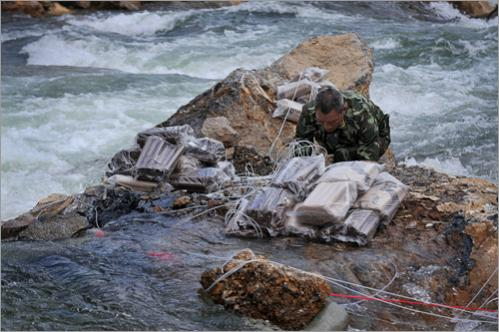 A soldier installs explosives at the Shibangou quake-formed lake to widen a channel to release water in earthquake-hit Qingchuan Sunday, June 8, 2008. A 'relatively strong' aftershock shook a massive quake-formed lake Sunday that had been threatening to flood more than 1 million people, sending landslides tumbling down surrounding mountains.
