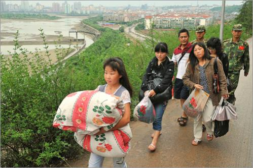 Earthquake survivors carry their belongings to move to higher ground as the drainage has begun at the swollen Tangjiashan quake lake at Mianyang on Saturday, June 7, 2008.