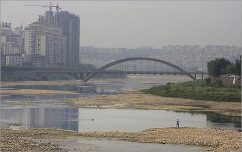 A resident tries to fish on the drained riverbed downstream of the Tangjiashan quake lake where a landslide had choked off the river runoff and now threatens to burst near Mianyang. Residents living in low-lying areas of Mianyang near the Fu river have been ordered to move to higher grounds in anticipation of the eventual release of water from the quake lake upstream in Tangjiashan.