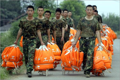 Soldiers carry life jackets in preparation for rescue efforts at the Tangjiashan earthquake lake in the town of Jiuling, Jiangyou county, Sichuan province on June 6, 2008.