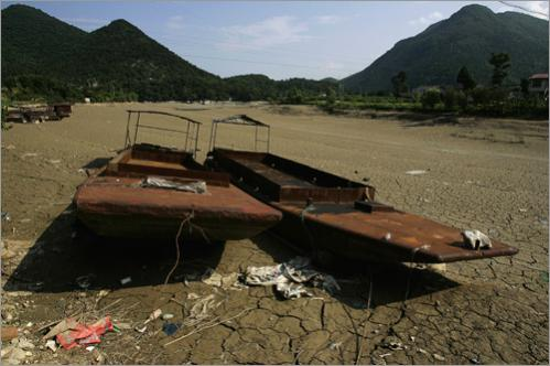 Boats are seen on the dried-up riverbed of the Tongkou river, downstream from the Tangjiashan quake lake on Monday, June 9, 2008. Floodwaters could reach the town within an hour if the Tangjiashan quake lake bursts, local patrolling soldiers said.