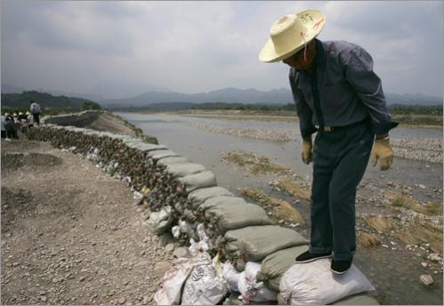 A local worker steps on bags of stones making up a temporary dam built against the possible coming floods in Huangtu town of Anxian county, Sichuan province June 8, 2008. Chinese troops on Saturday eased pressure on a swelling 'quake lake' threatening hundreds of thousands of people, but a smaller lake burst its banks in a show of destructive force.