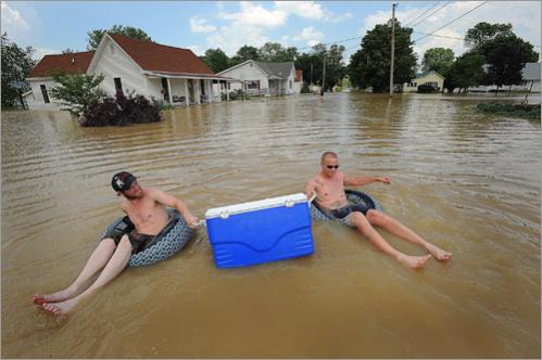 Ryan Lewis, left, and Joe Conway, right, float down 3rd Street toward their houses, carrying beverages in an ice cooler on Monday, June 9, 2008 in Worthington, Ind.