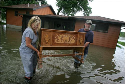 John Chase and his wife Beverly Chase carry furniture out of their flooded home on Monday, June 9, 2008, in Iowa City, Iowa.