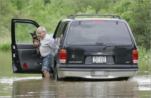 Abel Ortiz, holding his dog 'Chiquito,' wades out of his truck at his home on the flooded Elm Road in Oak Creek, Wis., Monday, June 9, 2008.