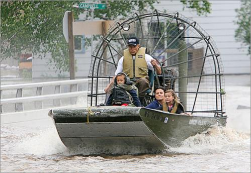 A family is evacuated by airboat Monday June 9, 2008 in Columbus, Wisc. Families living along the Crawfish River in Columbus that were trapped from the flooding waters were rescued by airboat and hovercraft.