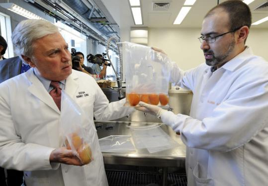 Microbiologist Amir Alavi (right), checks a bag of tomatoes as FDA Commissioner Andrew C. von Eschenbach looks on.