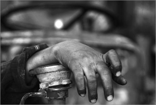 The hand of Palestinian mechanic Imad Qora'an, 13, is seen at the car garage where he works in Ramallah.
