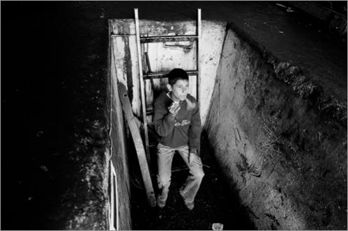 Palestinian mechanic Jihad Robin, 12, smokes a cigarette, at the car garage, where he works in the industrial area of Ramallah.