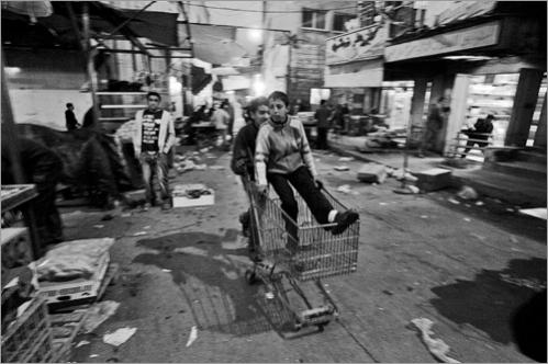 A Palestinian youth pushes his friend on a cart as they wait for customers who need goods transported in the fruit market in Ramallah.