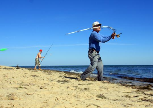 Bill Flynn of Weymouth and his grandson Mark Diamond, 21, of Bridgewater surfcast in Mashpee yesterday. The federal government intends to require anglers who might catch any species that travels between fresh and saltwater, such as striped bass, to register.