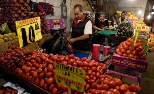 A tomato vendor worked at his stand in Mexico City yesterday. Mexican consumers can now buy top-quality tomatoes for a third less than normal prices.