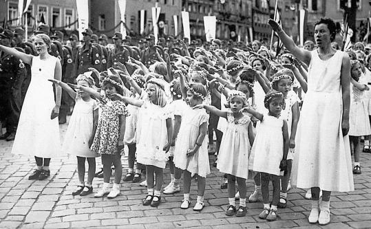 Little German girls learn the Nazi salute, a mandated yet impersonal form of greeting, in the late 1930s.