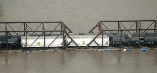 Freight cars are stranded on a bridge in Cedar Rapids, Iowa. Flooding in the Midwest has halted or delayed most shipping.