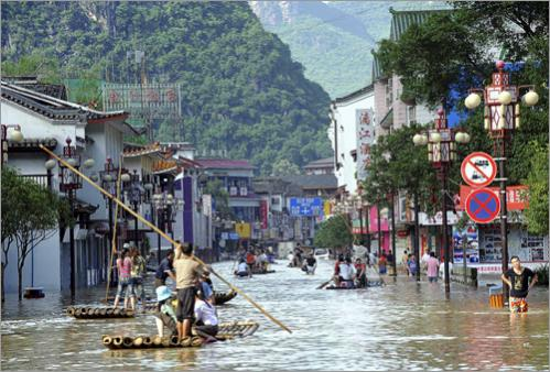Residents used rafts to sail through flooded streets in Yangshuo County in southwest China's Guangxi Zhuang Autonomous Region on Friday, June 13, 2008. Heavy rains in the region triggered floods that killed six people and forced the evacuation of 150,000 residents, state media reported Saturday.