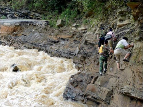 Residents walked along the edge of a collapsed road leading into Wangmo town in southwest China's Guizhou province on June 16, 2008.