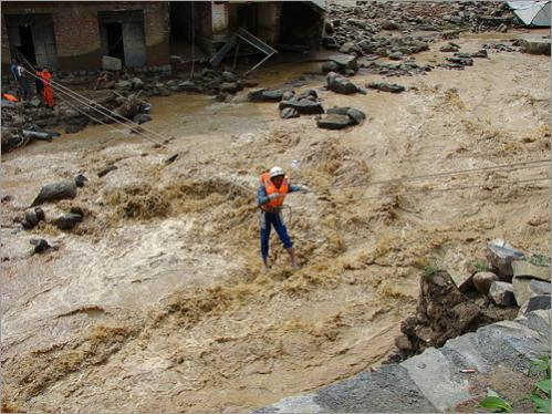 Rescuers evacuated residents trapped in their homes by rising flood water in Wangmo town on June 16, 2008.