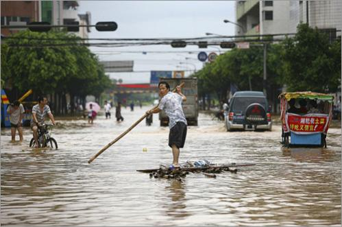 A resident paddled a homemade raft on a flooded street in Xiaojiejiao Village, Humen Township in Dongguan, in south China's Guangdong province Friday, June 13, 2008.