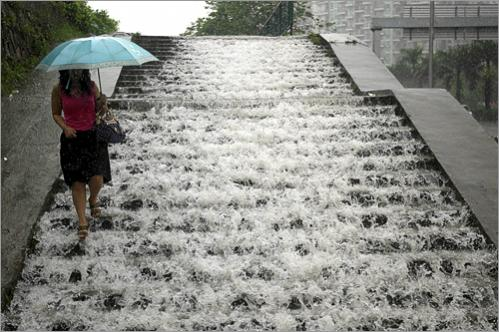 A resident walked down flooded steps in Shenzhen in south China's Guangdong province Sunday, June 15, 2008.