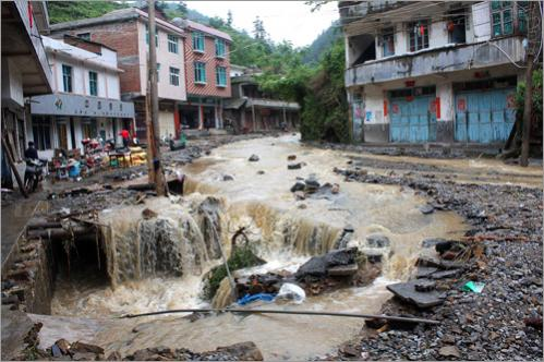 Flood waters flowed down a collapsed street in Wangmo town.