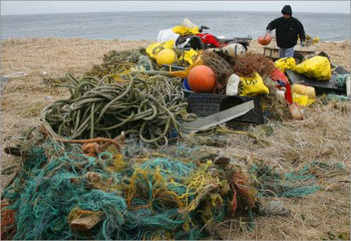 Andrew Fratis unloads an ATV used to haul debris collected from a beach on St. Paul Island, Alaska Thursday, June 6, 2008 during a cleanup on the Bering Sea island.