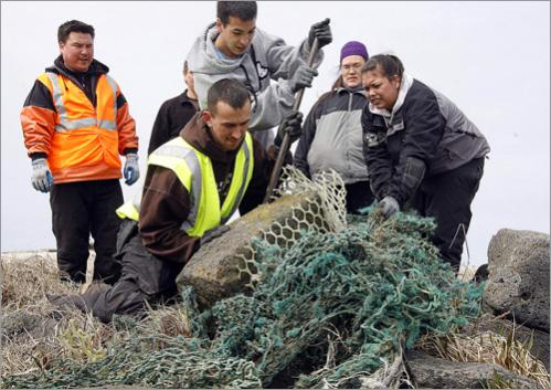 Crew members work to get a discarded commercial fishing net loose from a beach on St. Paul Island, Alaska, Monday, June 2, 2008.