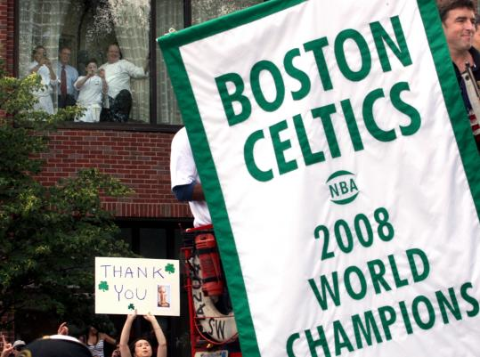 Celtics owner Wyc Grossbeck held the championship banner as the Celtics rolling rally passed the Four Seasons Hotel yesterday.