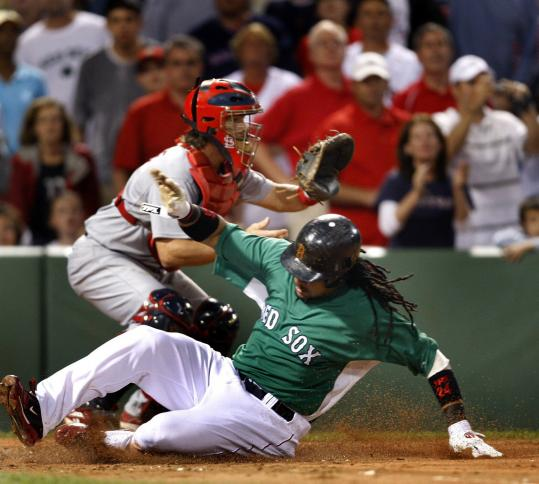 Manny Ramírez slides past Cardinals catcher Jason LaRue in the second inning with the run that gave the Red Sox a 1-0 lead. Ramírez scored on Julio Lugo's sacrifice fly.