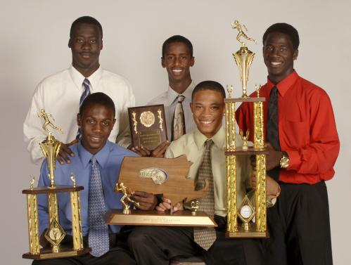 Forget the baton, pass the championship trophy. Members of Charlestown's decorated track team (back row, from left) Sheldon Allen, Omar Aden and Kareem Cutler. and (front row, from left) Yaovi Jondoh and Kamal Riley show off some of the Townies' trophies.