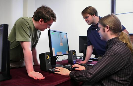 From left, Becker College students Andrew Silvernail, Patrick Walley, and James Grant test out their game Munch's Vacation, which caught the attention of Curt Schilling's 38 Studios.