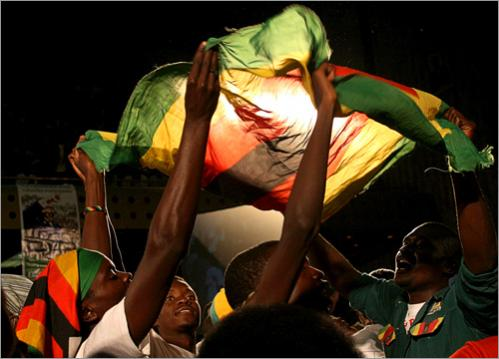 Supporters of Zimbabwean President Robert Mugabe raise a flag during an election rally for the ruling ZANU PF party's youth in Harare, Friday June 13, 2008. Zimbabwe's welfare minister ordered independent aid groups to stop field work last week, prompting charges that Mugabe was using food as a political weapon before the June 27 presidential runoff.