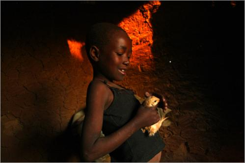 AIDS orphan Priscilla Moyo, 8, holds a young chick in her grandmother's hut in the countryside June 23, 2008 outside of Bulawayo, Zimbabwe. The nation slipped further into political chaos following the withdrawal of opposition leader Morgan Tsvangirai from the runoff presidential election June 27. President Robert Mugabe recently suspended food aid from international NGOs to the populace, causing a food crisis across the nation, especially in rural areas.