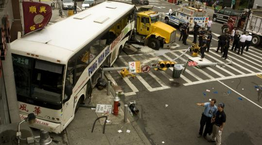 The scene at Bowery and Canal Street in New York, where a dump truck hit a Fung Wah bus boarding passengers for Boston.