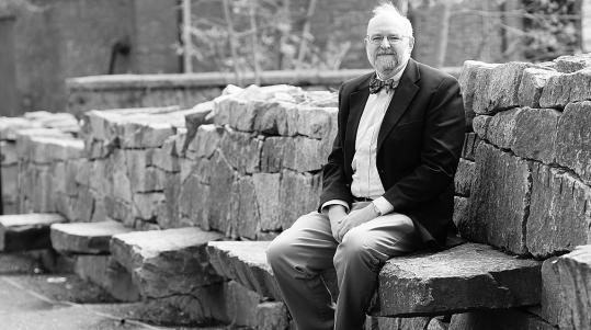 Emerson Baker, a Salem State College professor, has written a book about witchcraft hysteria in New Castle, N.H., in the late 1600s. Here he sits in the Witch Trials Memorial Park in Salem.